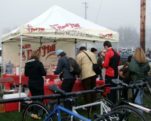 Cyclists and spectators line up to get hot oatmeal on a cold fall day.