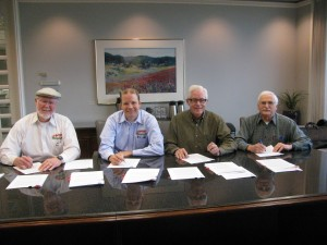 Partners Bob Moore, Robert Agnew, Dennis Gilliam and John Wagner sign over ownership of the company Tuesday morning.